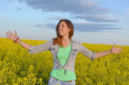 Beautiful girl posing in a field of yellow flowers photo