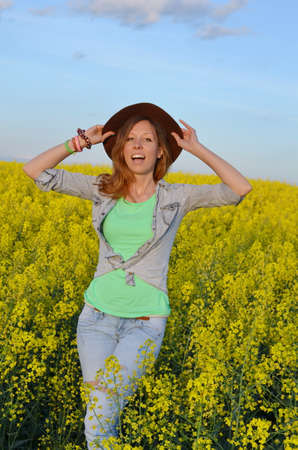Girl posing with a hat in a field of yellow flowers photo