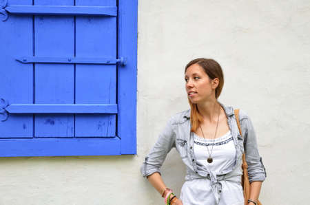 mid twenties: Young girl posing by the blue painted window shutters Stock Photo