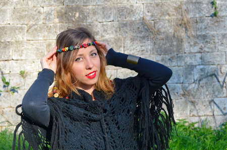 mid twenties: Hippy girl posing with colorful necklaces around her head outdoors