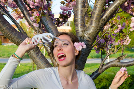 mid twenties: Happy girl posing with big party sunglasses outdoors with flower in her hair