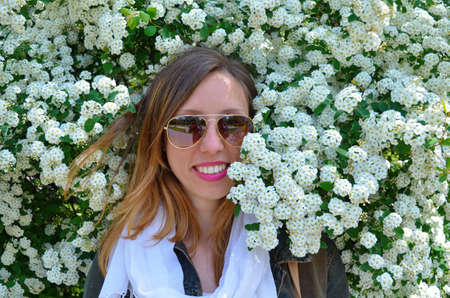 Happy young girl wearing sunglasses posing surrounded by flowers