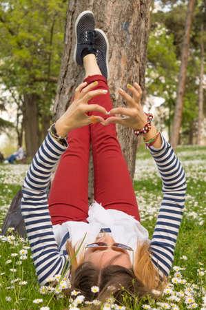 mid twenties: Bunette girl lying in the grass full of flowers Stock Photo