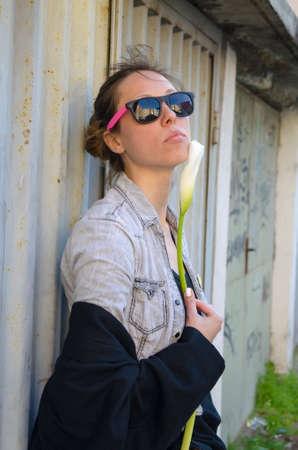 mid twenties: Brunette girl posing with a flower by the garage door, wearing funny sunglasses