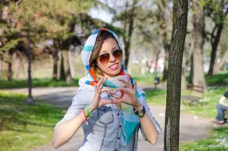 bandana girl: Girl enjoying spring wearing a colorful bandana and making a heartshape with her hands Stock Photo