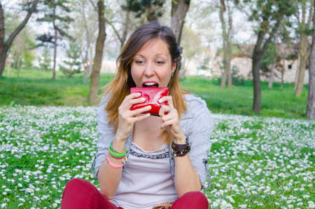 Brunette broke in spring trying to eat her wallet among the daisies
