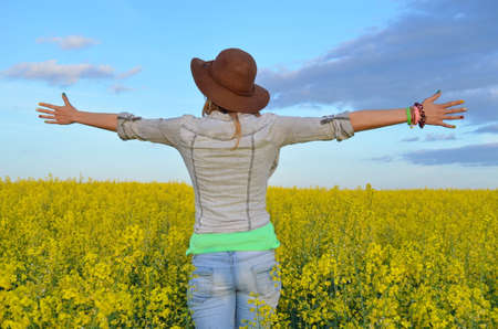 Girl posing with a hat in a field of yellow flowers