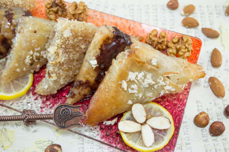 Greek baklava decorated with nuts, lemon and almonds on a decoupage table