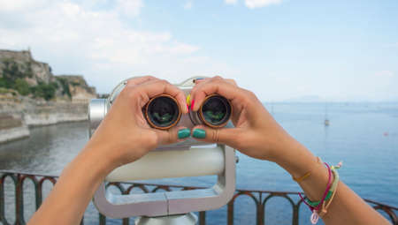 observable: Young girl hands with colourful painted nails holding public binoculars with seaside view