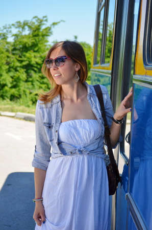 old bus: Young girl entering an old bus in summer