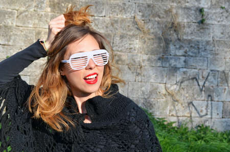 mid twenties: Happy girl posing with big party sunglasses outdoors