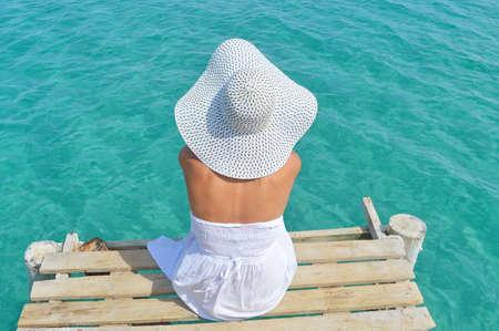 vestido blanco: Mujer joven en un vestido blanco mirando el mar desde un muelle