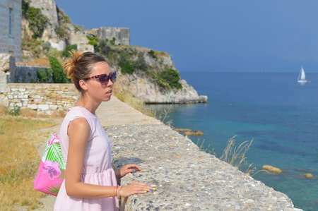 kerkyra: Girl looking at the sea from the new fortress in kerkyra wearing pink dress and sunglasses Archivio Fotografico