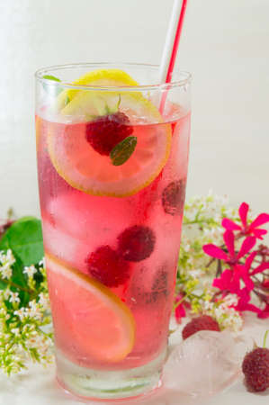 colorful: Homemade raspberry ice tea with lemon raspberry and ice cubes on a table decorated with flowers Stock Photo