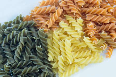 unprepared: Tri-Color unprepared macaroni pasta stacked to form background