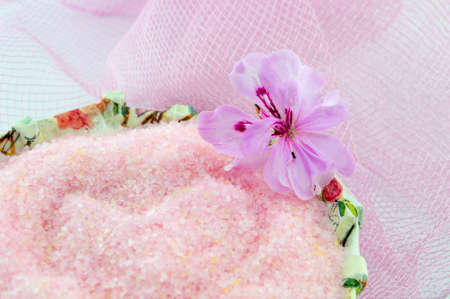 decoupage: Pink flower with pink bath salt in a decoupage decorated  bowl on pink textured background