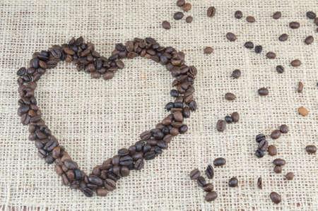 granos de cafe: Granos de caf� en forma de coraz�n colocados en una bolsa de caf� con granos de caf� esparcidos Foto de archivo