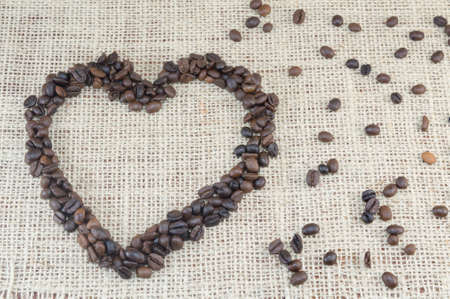scattered in heart shaped: Heart shaped coffee grains placed on a coffee bag with scattered coffee grains Stock Photo