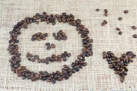 granos de cafe: Smiley cara y la forma del corazón hecha enteramente fuera de los granos de café colocada en la bolsa de café de textura Foto de archivo
