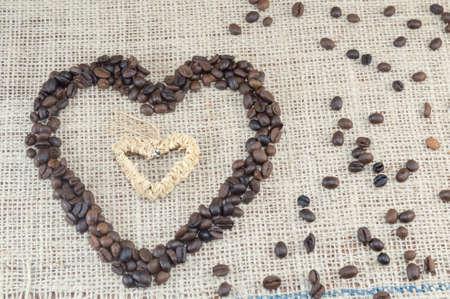 granos de cafe: Granos de café en forma de corazón colocados en una bolsa de café con granos de café esparcidos Foto de archivo