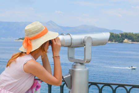 pink dress: Young girl looking thru public binoculars at the seaside wearing straw hat and pink dress Stock Photo