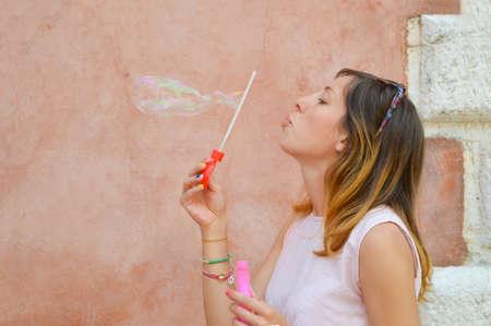 burbujas de jabon: Ni�a soplando burbujas de jab�n contra el tel�n de fondo colorido con un vestido de color rosa