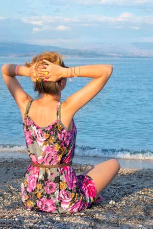 cabeza femenina: Muchacha con las manos detrás de la cabeza de relax con la vista en el mar