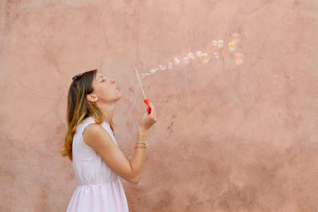 pink dress: Girl blowing soap bubbles against colourful backdrop wearing pink dress Stock Photo