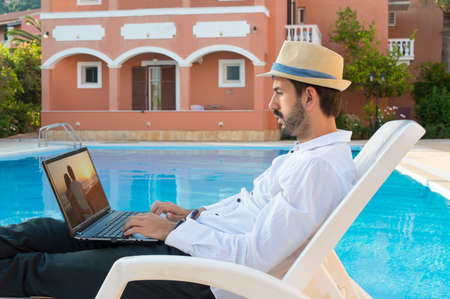 lap top: Young bussines man on pause while working on his lap top by the pool while on vacation  wearing straw hat