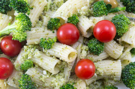 Pasta with broccoli and whole cherry tomatoes served close-up
