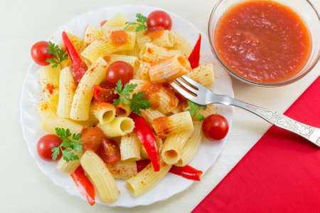Macaroni with cherry tomatoes, parsley and red pepper served with a tomato sauce and a fork, on a table with red napkin