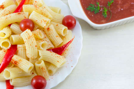 dinner plate: Pasta with cherry tomatoes and red pepper served with a tomato sauce close up