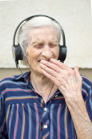 old people: Ninety years old grandma reaction while listening to modern music. Grandma listening to music on headphones Stock Photo