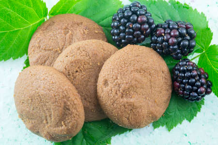 integral: Integral biscuits and fresh blackberries on blackberry leaves. Healthy dessert