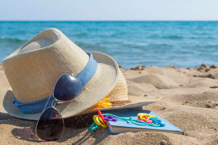 glasses in the sand: Summer straw hats, sunglasses and a book on the beach. Summer vacation accessories Stock Photo