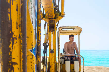 construction machinery: Young man operating the bulldozer at the beach on a hot summer day