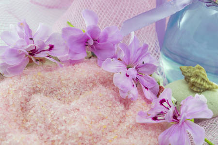 aroma therapy: Pink flower rounding pink bath salt with etheric oil in a bottle on pink background. Aroma therapy