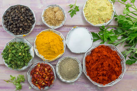 nautral: Various spices in shiny bowls on a purple colored wooden table