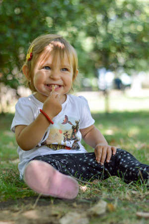 inocent: Cute one year old baby girl sitting on grass in a park Stock Photo