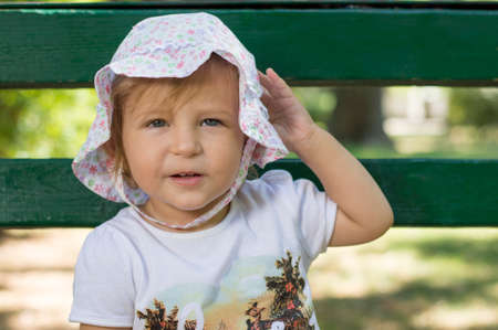one year: Adorable one year old baby portrait in a park wearing funny hat