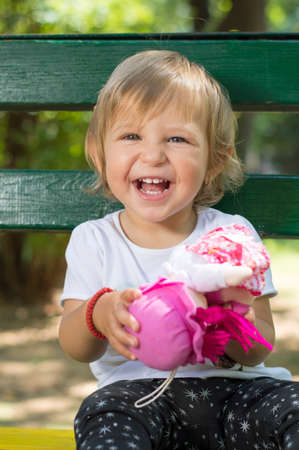 inocent: Adorable one year old baby girl with blue eyes sitting on a bench in  a park with a doll in her hands Stock Photo