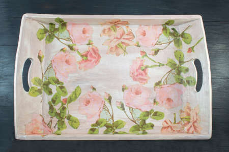 Decoupage decorated tray with flower pattern against  black wooden background. Decoupage tehnique decoration 스톡 콘텐츠