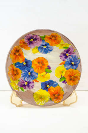 decoupage: Decoupage decorated plate with flower pattern against  white wooden background. Decoupage tehnique example Stock Photo