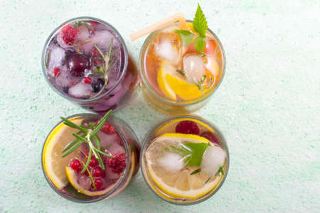 Four non alcoholic fruit cocktails arranged on the green table top view. Cold drinks
