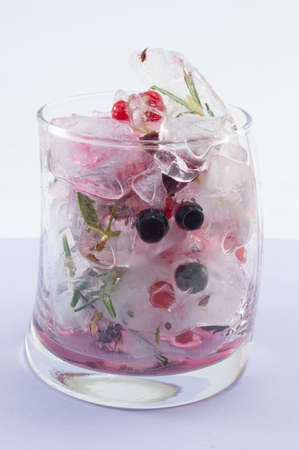 cool background: Red forest fruit cocktail with ice, lemon and sliced fruits in a crooked glass on purple background