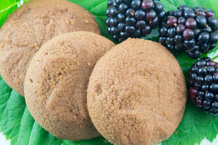 Integral biscuits and fresh blackberries on blackberry leaves. Healthy dessert
