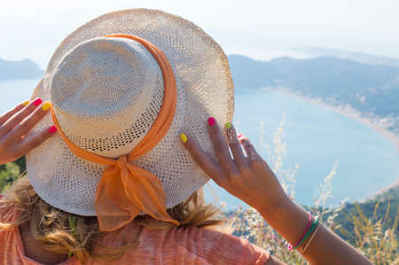 sommerferien: Junges M�dchen mit Strohhut Blick auf das Meer vom Berg Sicht. Sommerferien Lizenzfreie Bilder