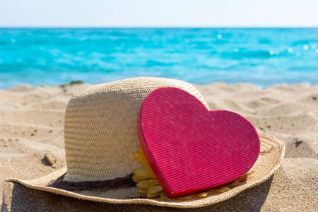 Straw hat and a heart shape on the sandy beach. Summer love abstract 스톡 콘텐츠