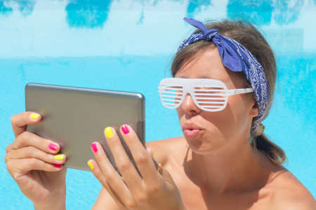 funy: Beautifull young girl making selfie by the pool with tablet