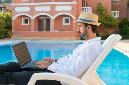 hard work: Young bussines man working on his lap top by the pool while on vacation  wearing straw hat